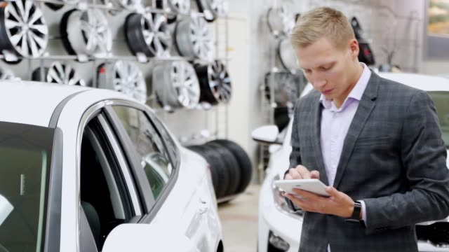 Man seller with tablet shows the car in the showroom. Successful salesman standing in front of modern vehicle demonstrates shows car and looks in camera, smiling. Concept of car selling