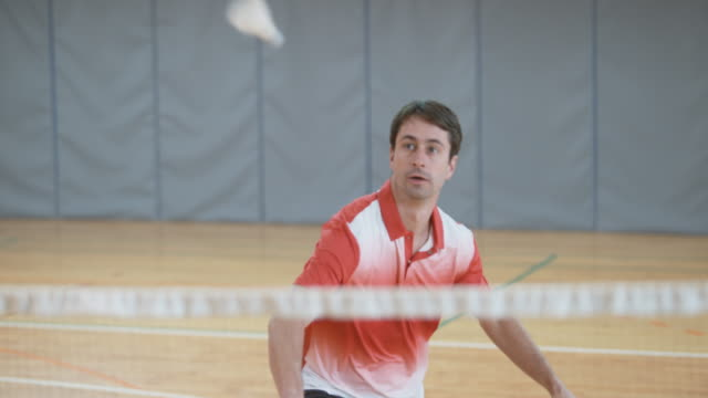 Man serving and playing indoor badminton video