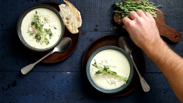 Man serving creamy caulflower and broccoli with feta soup