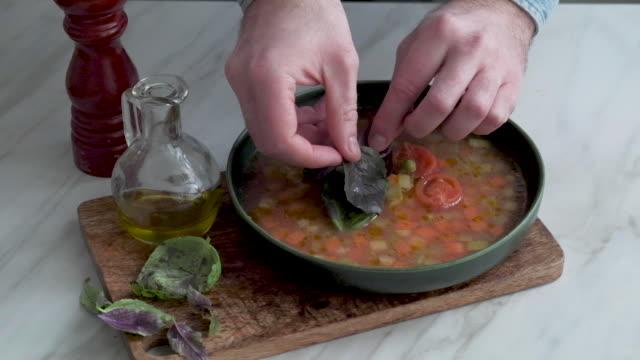 stockvideo's en b-roll-footage met mens die minestronesoep dient - groentesoep