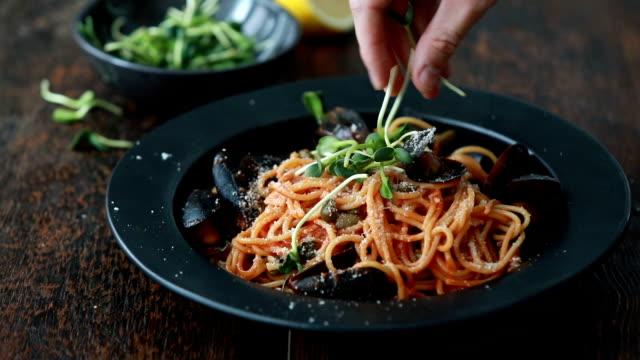 Man serving spaghetti with smoky tomato & seafood sauce