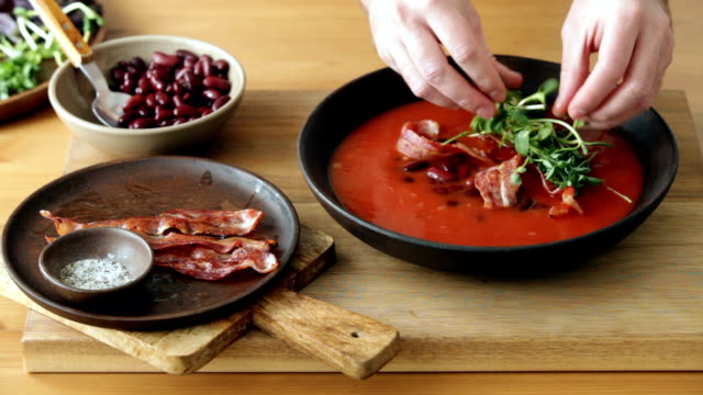 man serving spicy tomato, bean, herb and fried bacon soup - erba medica video stock e b–roll