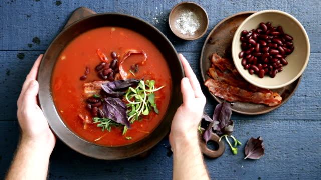 man serving spicy tomato, bean, herb and fried bacon soup - talerz filmów i materiałów b-roll