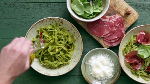 Man serving spinach pasta with basil pesto and prosciutto Man serving spinach pasta with basil pesto and prosciutto on green background pesto sauce stock videos & royalty-free footage