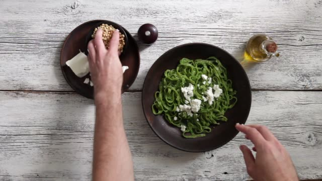 Man serving spinach pasta with creamy broccoli pesto, pine nuts and feta Man serving spinach pasta with  creamy broccoli pesto, pine nuts and feta on white background pesto sauce stock videos & royalty-free footage
