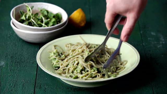 Man serving summer vegetarian pasta with broccoli pesto, peas and mint Summer vegetarian pasta with broccoli pesto, peas and mint on dark green background pesto sauce stock videos & royalty-free footage