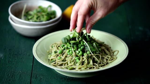 man som serverar sommar vegetarisk pasta med broccoli pesto, ärtor och mynta - pea sprouts bildbanksvideor och videomaterial från bakom kulisserna