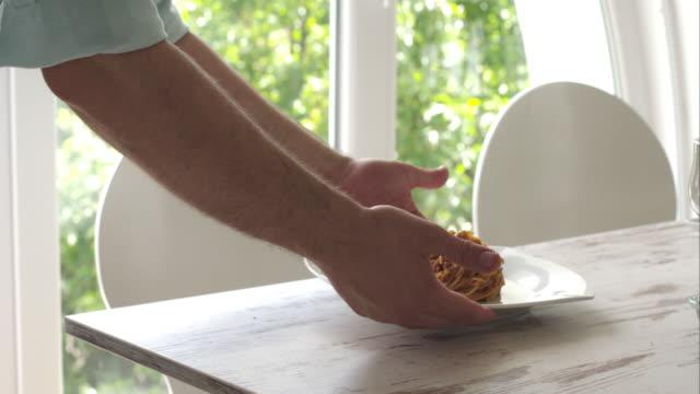 Man serving vegetarian spaghetti on the table video