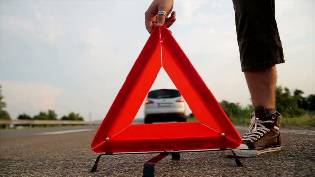 vídeos de stock e filmes b-roll de man set warning triangle on the road - berma da estrada