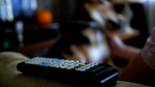Man sets remote control down on couch after picking a channel