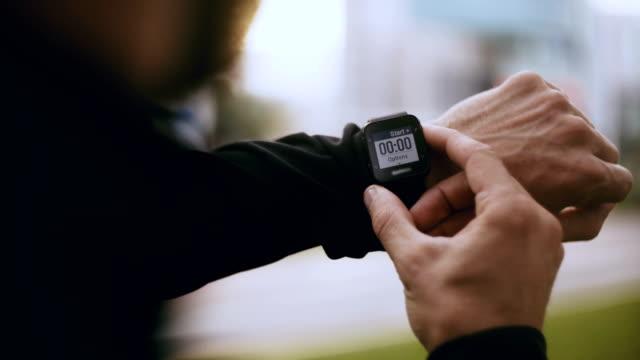vidéos et rushes de 4k homme définit la minuterie de veille intelligent, s'exécute hors de discussion. athlète commence une horloge tracker smart avant de faire du jogging dans la ville - chrono sport