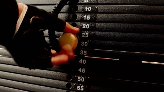 男のトレーナーに右の重量を設定 - 重い点の映像素材/bロール