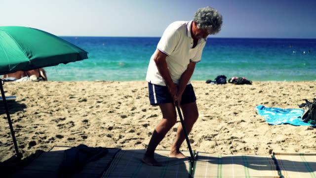 Man setting up beach umbrella video