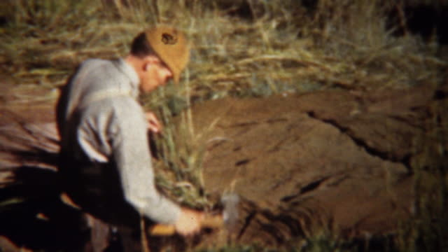 1940: Man setting up hunting blind camping tent with axe hammer. video