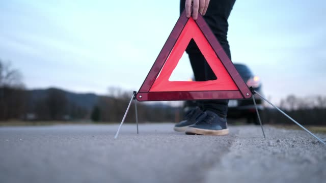 Man setting up warning triangle Man setting up warning triangle in the street with a broken car in the back warning sign stock videos & royalty-free footage
