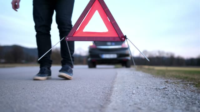 man setting up warning triangle - road signs stock videos and b-roll footage