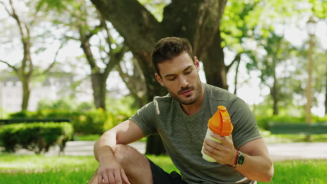 A man shaking and drinking his protein shake after exercise A young man sitting down in the park to drink his nutritional protein shake after his exercise. He is shaking the bottle, then drinking it. protein stock videos & royalty-free footage