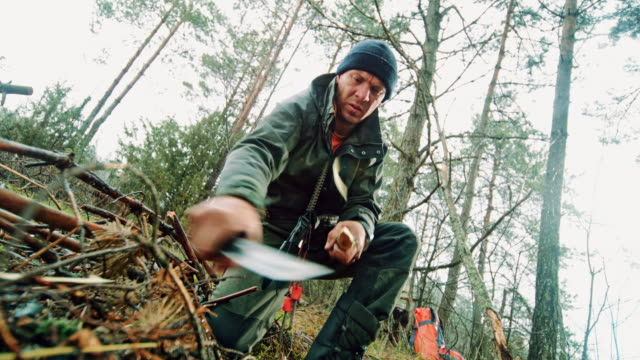 slo mo man sharpening a branch in nature using his knife - дикая местность стоковые видео и кадры b-roll