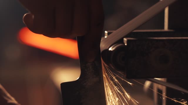 Man sharpening knife with sparks. Work on a sharpening machine.
