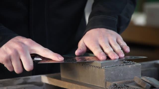 man sharpening sushi knife at japan fish market - slow motion - tradycja filmów i materiałów b-roll