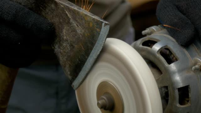 A man sharpens a big ax. video