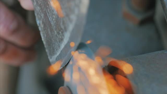 男は火花とマシンで斧をシャープします。 - 機械部品点の映像素材/bロール