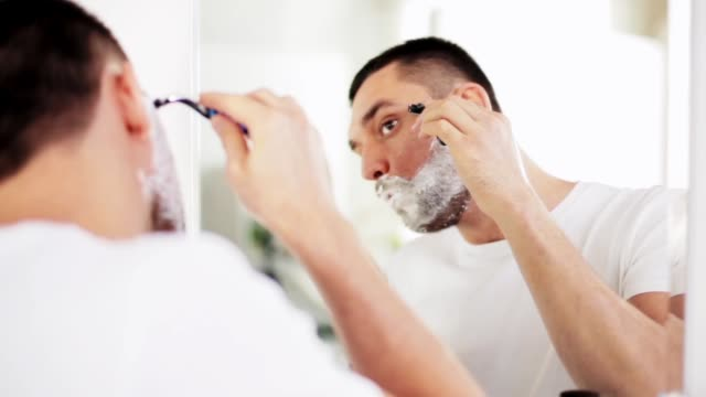 man shaving beard with safety razor at bathroom