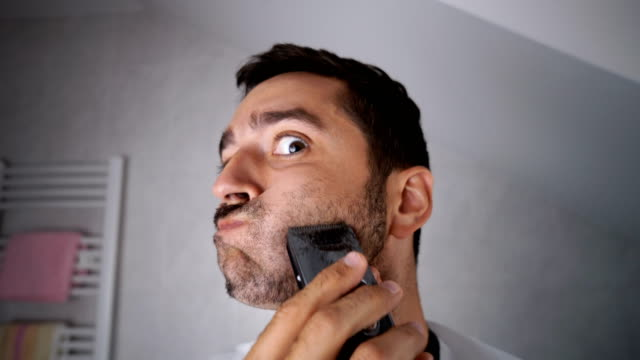 man shaving beard with trimmer - baffo peluria del viso video stock e b–roll