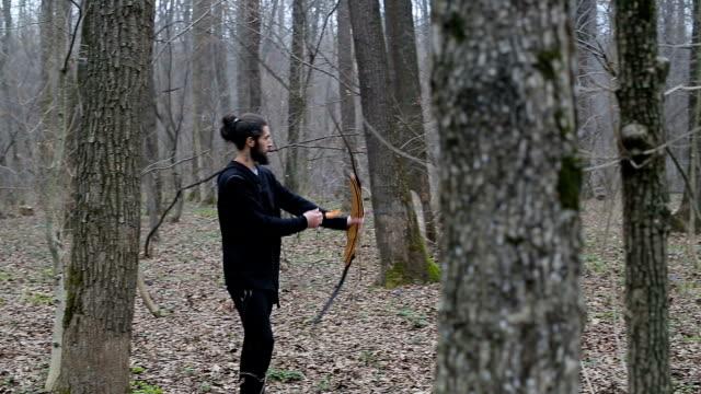 stockvideo's en b-roll-footage met man schieten met een boog in het bos - boog architectonisch element