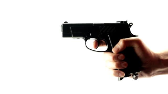 mann schießt eine schwarze pistole auf weißem hintergrund - trefferversuch stock-videos und b-roll-filmmaterial