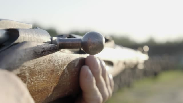 A man shoots a old rifle. Close up