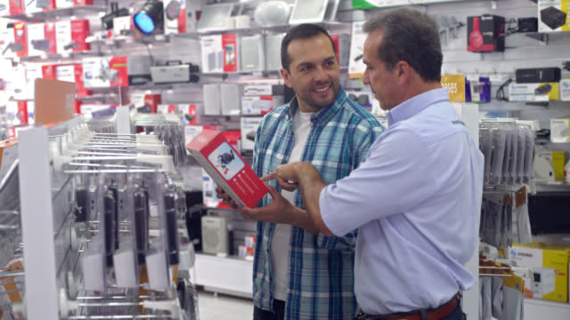 Man shopping at a tech store Casual man shopping at a tech store and salesman helping him electrical equipment stock videos & royalty-free footage
