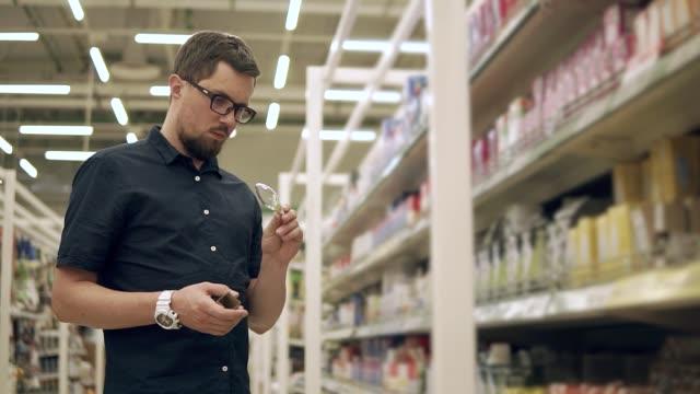 mann im baumarkt einkaufen. - led leuchtmittel stock-videos und b-roll-filmmaterial