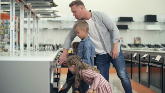 Man Shopping in Home Appliance Store with Little Daughters and Son Two little sisters and brother of elementary age looking inside of kitchen oven and discussing it with father while shopping in home appliance store appliance stock videos & royalty-free footage
