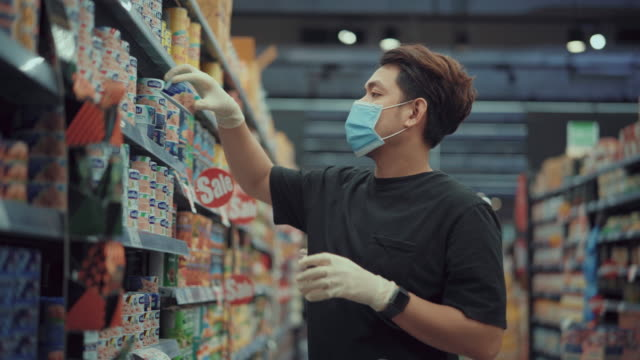 Man Shopping in market ,Covid-19 Asian man wearing latex gloves and a face mask is examining some meat products in a grocery store,Disinfecting groceries during COVID-19 grocery aisle stock videos & royalty-free footage