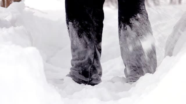 Man shoveling mass of snow in winter garden video
