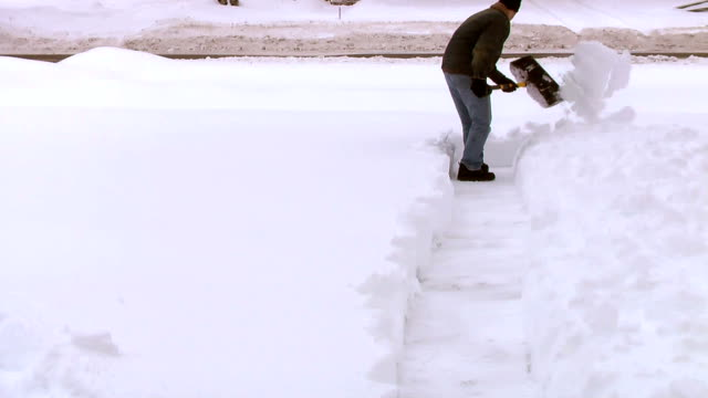 Man Shoveling Snow from Sidewalk video
