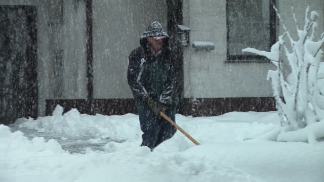 WS, PAN, Man shoveling snow on driveway, Vrhnika, Notranjska region, Slovenia