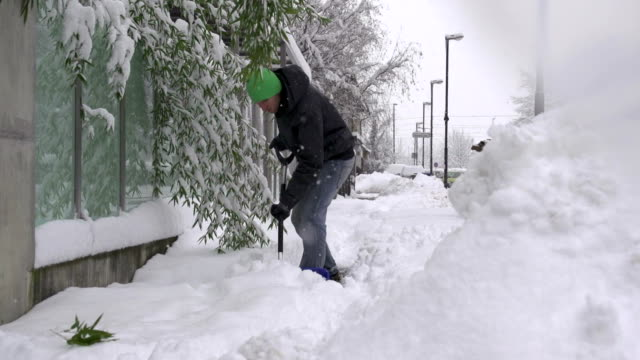 Man shoveling snowy sidewalk video