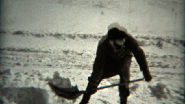 1936: Man shovels snow at camera in fedora hat and scarf wrapped head.