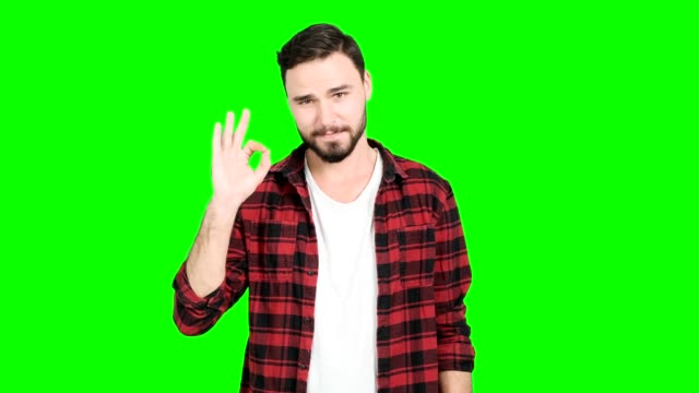 Man showing okay sign on green screen.