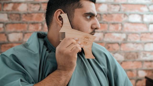 Man showing wooden beard shaving tool
