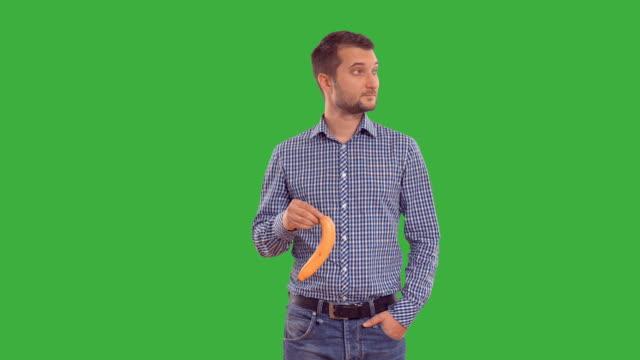 man shows copy space and enjoys on a green background - penis stok videoları ve detay görüntü çekimi