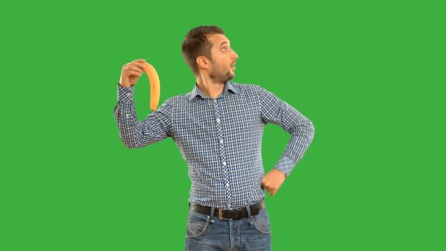 man shows copy space and smiling on a green background - penis stok videoları ve detay görüntü çekimi