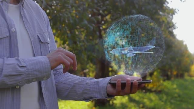 man shows hologram with passenger aircraft - skrzydło samolotu filmów i materiałów b-roll