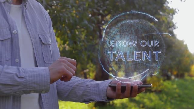 Man shows hologram with text Grow our talent