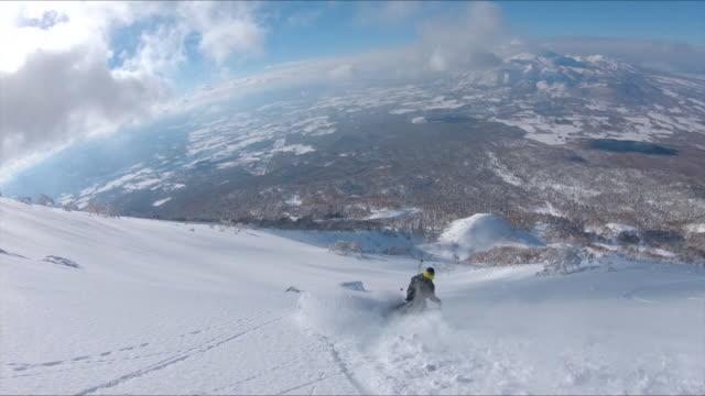 antenn: man fragmentering snöiga fjällterräng medan på roliga skidresa i japan. - hokkaido bildbanksvideor och videomaterial från bakom kulisserna