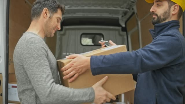 Man signing digitally for the package by the delivery van
