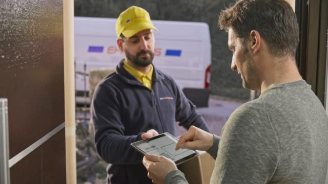 Man signing for the package being delivered to his front door by a male courier