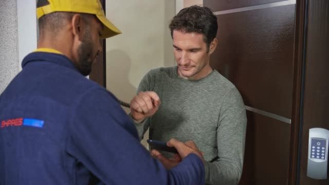 Man signing the digital POD before the male courier hands him the package at the front door